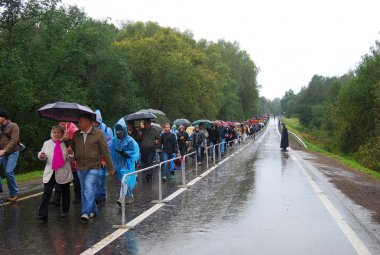 People crowds walk under the umbrellas on the wet road.