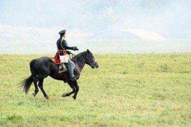 Reenactor dressed as Napoleonic war soldier rides a horse.
