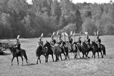 Reenactors dressed as Napoleonic war soldiers ride horses