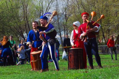 Musicians in historical costumes perform in a park