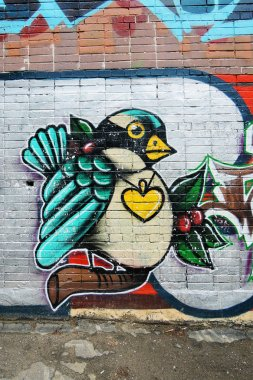 A bird painted on a brick wall.