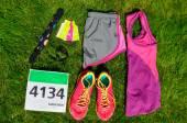 Fényképek Futócipő, a maraton rajtszámot (szám), a futók hajtómű- és energia gélek fű háttér, sport, fitness és egészséges életmód fogalma