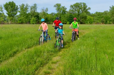 Happy family on bikes, cycling with children