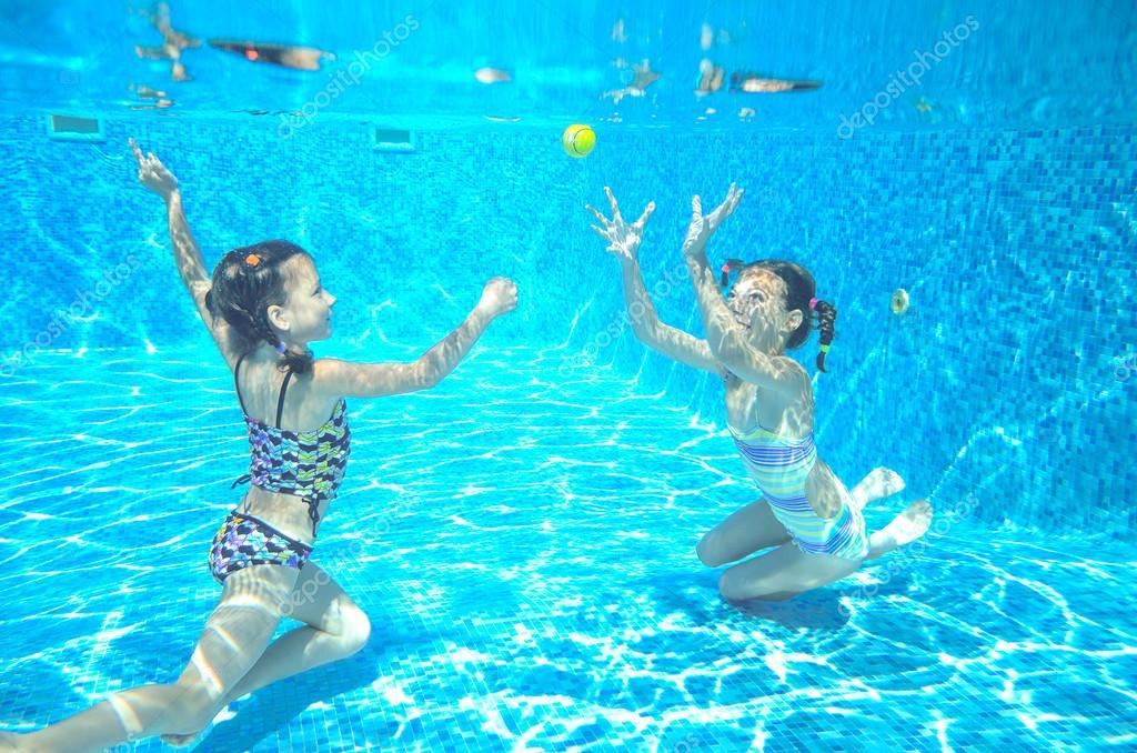ni os felices nadan en la piscina bajo el agua chicas de