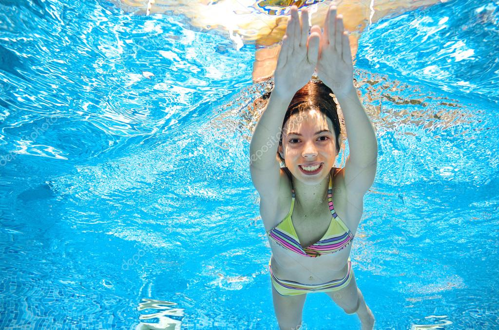 Child swims in pool underwater, happy active girl in goggles has fun under water, kid sport on family vacation