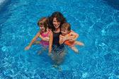 šťastná rodina baví v bazénu na letní prázdniny, matka a děti