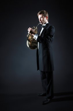 French horn player with music instrument