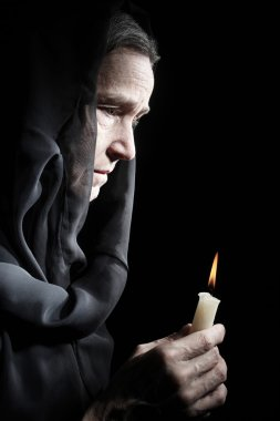 Senior woman with candle in sadness