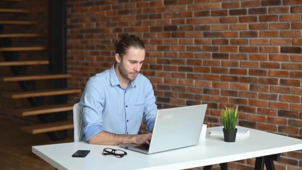 A hipster guy is using a laptop indoor