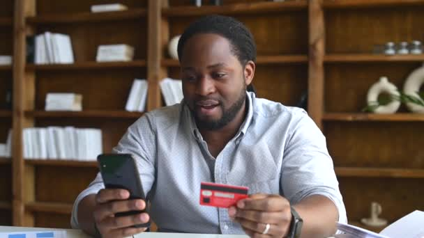 Sad African-American guy with phone and credit card