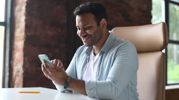 Glücklicher indischer junger Mann sitzt am Schreibtisch, hält und benutzt Smartphone