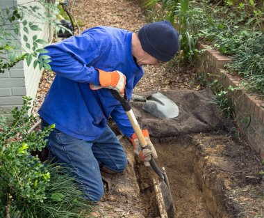 Man Digging Trench to Replace Sewer Line Pipes and Lawn Sprinkle