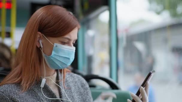 cestující v lékařské masce a rukavicích dekontaminuje mobilní telefon antiseptikem v důsledku pandemie koronaviru při cestování veřejnou dopravou
