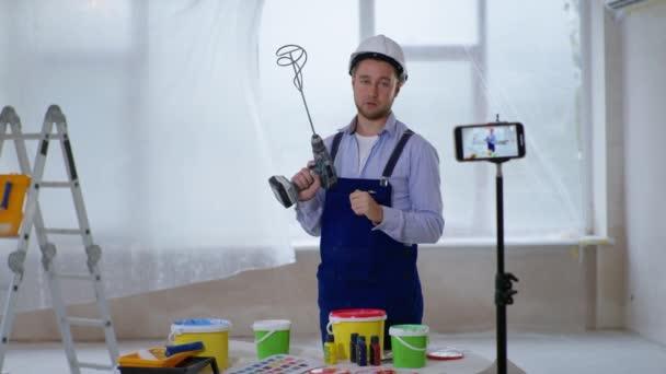 Hausmaler nimmt Video auf Smartphone auf und mischt Farbe in Eimer zum Streichen von Wänden im Haus mit Baubohrer