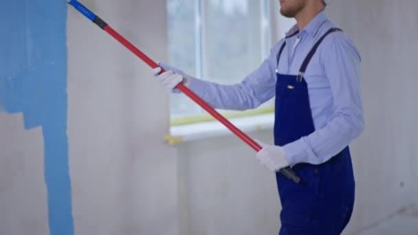 Malermeister bemalt Wände von Hand mit Walze bei Renovierungen, Hausbau