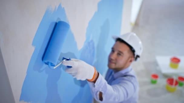 Wohnung Renovierung und Hausbau während der Renovierung und Verbesserung, führt junge Maler Finishing-Arbeiten verwendet Walze, um Wände zu streichen