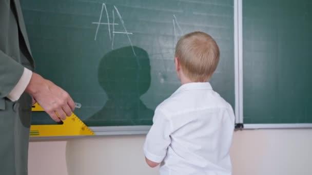 fiú downs szindróma levelet ír fehér kréta a táblán, a tanuló örül a sikernek, és ad öt a tanár az osztályteremben