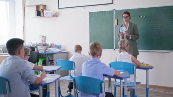 általános iskola, pedagógus mutatja tanulók kártyák levelekkel, okos gyerekek felemeli a kezét tudja a helyes választ ül asztalok osztályteremben