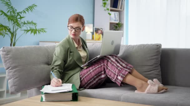 woman in jacket and pajamas works remotely in home office finishes work on laptop and holding hands behind head while lying on sofa at home