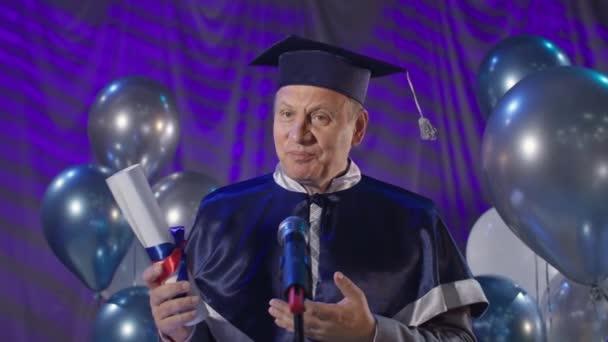 mužský rektor v akademickém klobouku a plášti blahopřeje studentům s promocí na vysoké škole, mluví do mikrofonu, zatímco stojí v konferenčním sále pozadí balónů