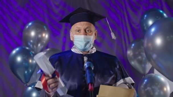Diplom on-line, muž univerzitní profesor nosit lékařskou masku na ochranu proti viru a infekci předkládá osvědčení o školení absolventů prostřednictvím video odkaz a mail