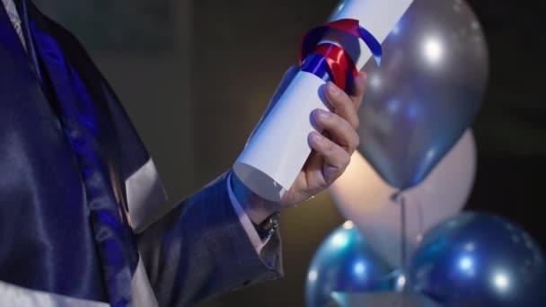 mužský profesor s diplomem v ruce provádí slavnostní ceremoniál předložení osvědčení o absolvování studia studentům, detailní záběr