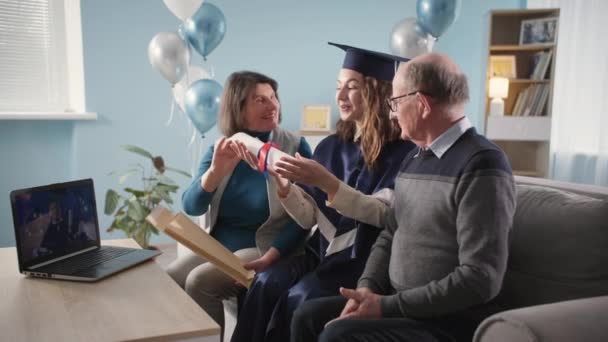 online graduation ceremony, happy female graduate in academic gown and hat with parents rejoices at being awarded diploma