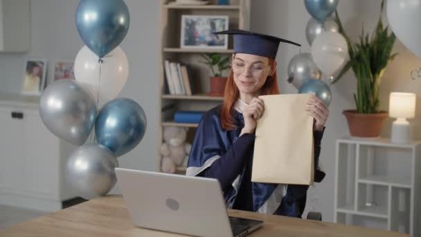 promoce on-line, šťastná mladá žena v akademických šatech a klobouk komunikuje prostřednictvím videohovoru na notebooku a ukazuje svůj diplom své rodině během pandemie a karantény
