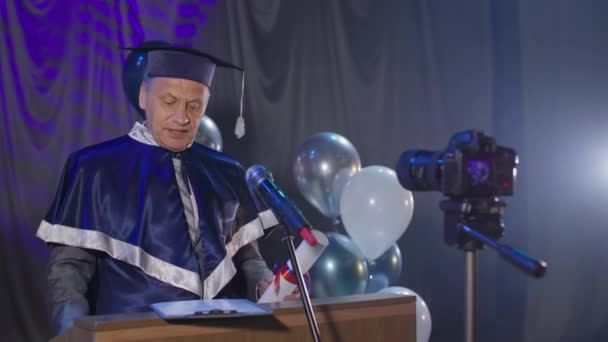 šťastný vysokoškolský učitel blahopřeje absolventům na konci akademického roku a představuje jim diplomy on-line přes video odkaz stojící na židli v konferenčním sále, pandemie