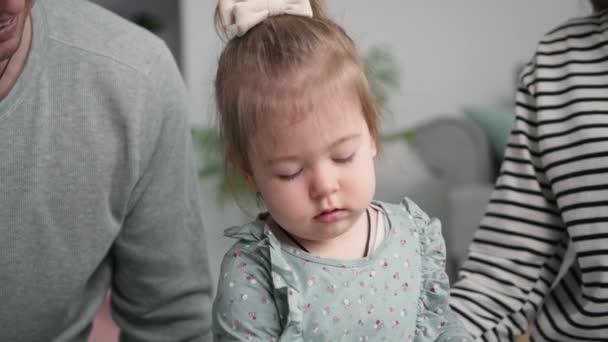 Porträt eines fröhlich lächelnden kleinen Mädchens, das während eines Familienurlaubs zu Hause Spiele mit seinen Eltern genießt, lächelt und in die Kamera blickt