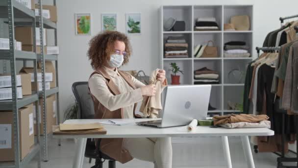 Einzelhandelsgeschäft, glückliche Verkäuferin mit medizinischer Maske freut sich über gute Online-Shopverkäufe am Tisch in der Modeboutique und wirft Hände hinter den Kopf