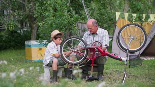 Kindererziehung, fürsorglicher älterer Mann mit Junge im Hut haben Spaß und reparieren im Sommer im Garten ein Rad