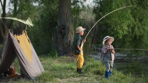životní styl, roztomilé mužské děti v kloboucích s rybářskými pruty v rukou baví rybaření v rybníku a relaxaci venku na pozadí wigwam a zelené stromy