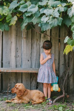 country girl with her dog under vine. wooden background