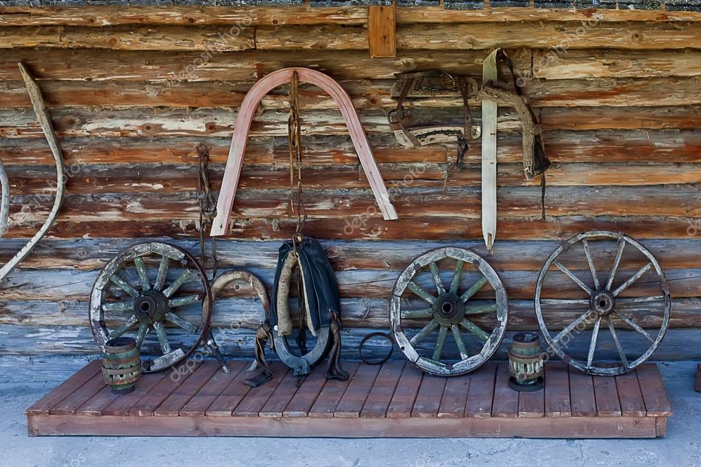 Log wall with parts of old carts — Stock Photo