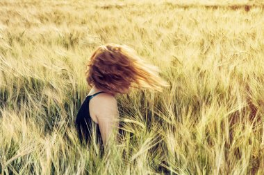 Young caucasian woman throws with her hair in wheat field