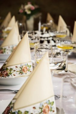 Set banquet table, decorative napkins and glasses with vermouth