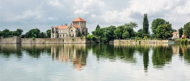 Beautiful castle with greenery and cloudy sky in Tata, Hungary