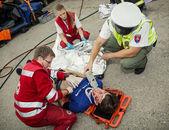 Sanitäter stabilisieren den Patienten. Polizist macht den Atem t