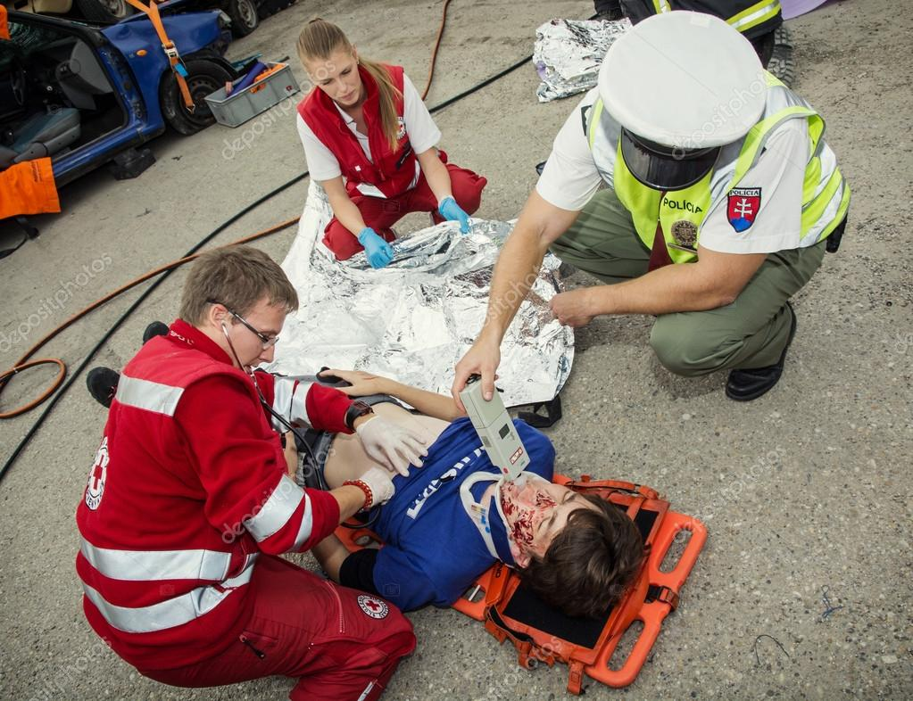 Paramedics stabilizing the patient. Policeman makes the breath t