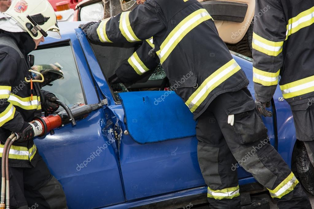 Firemen opening the car doors with hydraulic scissors