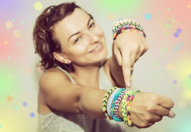 Young beautiful brunette with colorful rubber bracelets on her h