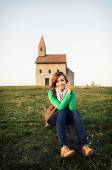 Fotografie Mladá žena sedí před kostelem