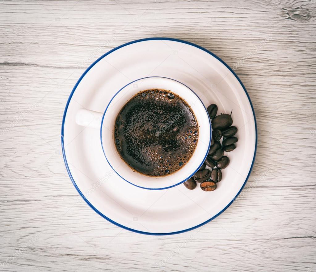 Ceramic cup of coffee with coffee beans, pick-me-up, morning