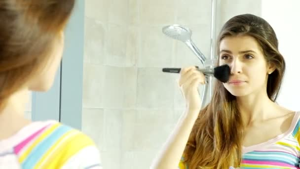 Cute young woman starting to put makeup on face in front of mirror in bath– stock footage