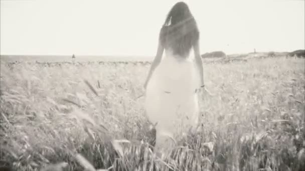 Black and white portrait of woman walking in cornfield in front of ocean