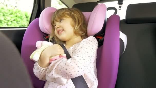 Happy baby girl sitting in car singing hugging plush toy 4K