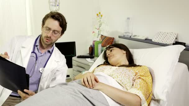 Doctor showing test results to woman lying in hospital bed dolly shot 4K