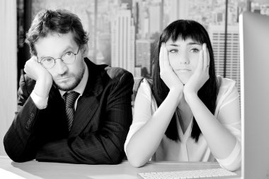 Black and white portrait of sad business people sitting in office