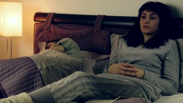 Smutná žena s manželem v posteli